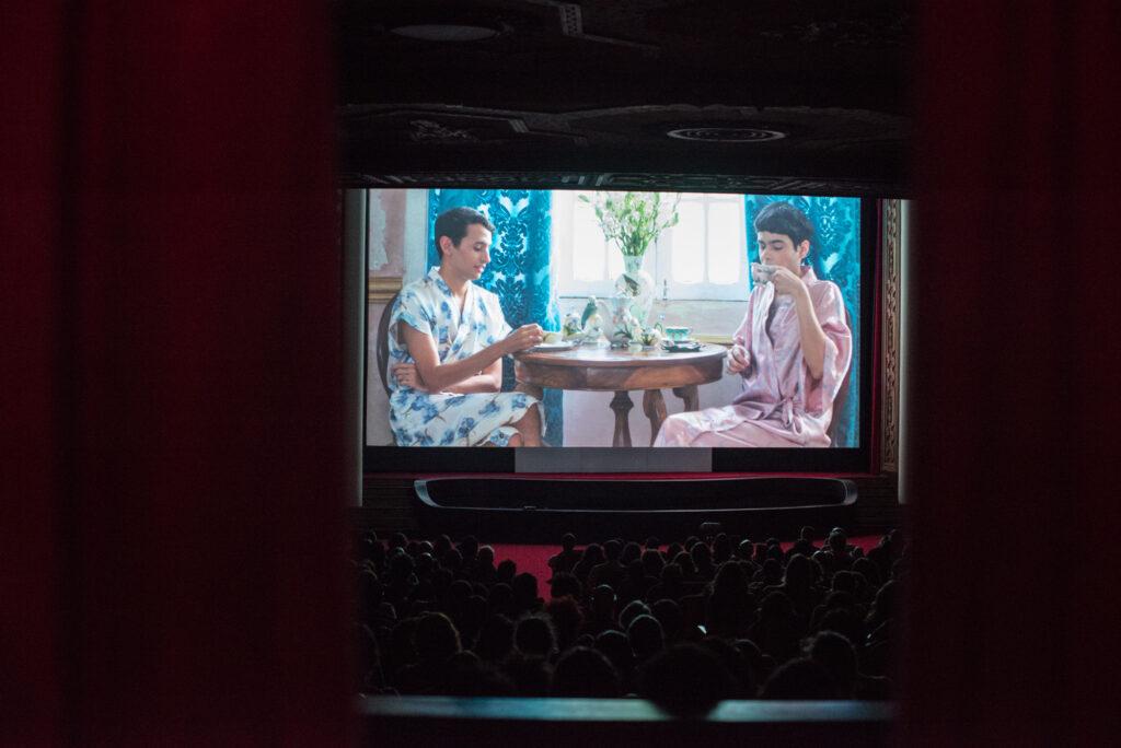 Imagem colorida de uma sala de cinema. No ambiente escuro, uma plateia cheia assiste a um filme em uma tela grande. Na tela, um filme mostra dois personagens tomando chá em uma sala de estar. Um dos personagens veste um robe branco com estampas azuis. O outro um robe de cor rosa. Entre ambos, uma mesa de madeira, uma vaso com plantas, xícaras e pires.